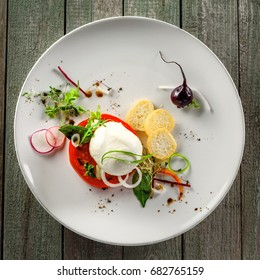 Classic Italian cuisine meal made of mozzarella, tomato and herbs on a table. Caprese salad on a white round plate.