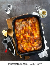 classic Italian eggplant Lasagna with vegetables and red wine in baking dish on a gray stone background .spilled parmesan, rosemary, old spoon . View from above. Italian food.