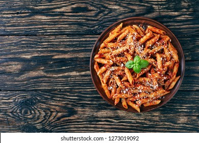 classic italian penne arrabiata  in a clay bowl with basil and freshly grated peccorino cheese on a rustic wooden table, view from above, flatlay, copy space for text left