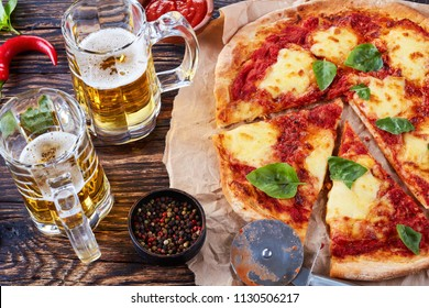 classic italian Pizza Margherita cut in slices on a parchments paper on a old rustic wooden table with beer in glass cups,  authentic recipe, view from above, close-up