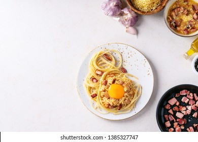 Classic Italian Spaghetti pasta alla carbonara with egg yolk in white ceramic plate served with cheese in wooden bowl and carbonara sauce over white texture background. Top view, flat lay, copy space