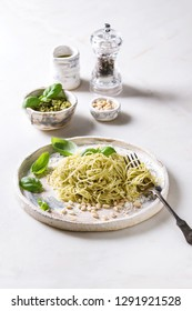 Classic italian spaghetti pasta with pesto sauce, pine nuts, olive oil and fresh basil. Served in ceramic plate with fork and ingredients above over white marble table