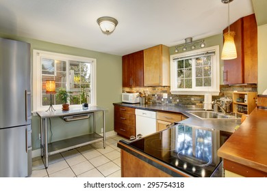 Classic kitchen in luxury home with white tile floor, and stainless steel fridge.