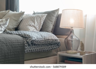 classic lamp style with alarm clock on table side in cozy bedroom interior design