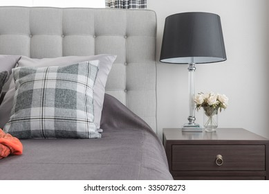 classic lamp style with vase of flower on wooden bedside table in classic bedroom