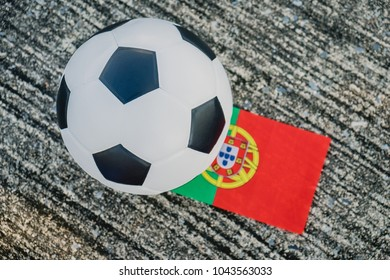 Classic leather soccer ball with Portugal national flag of the participating countries in the tournament on the street.
