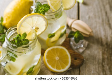 classic lemonade in glass jars, wood background