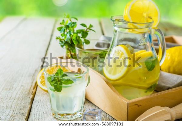 Classic lemonade in glass jars, wood background, outside