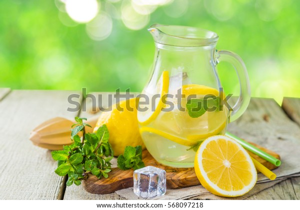 Classic lemonade in glass jars, wood background, outside