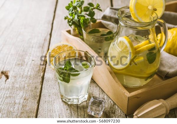 Classic lemonade in glass jars, wood background