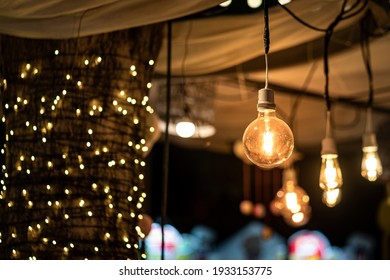 Classic lighting bulb in orange warm light shade during it glowing with blurred of other bulbs as bokeh background. Object for interior decoration, selective focus photo.