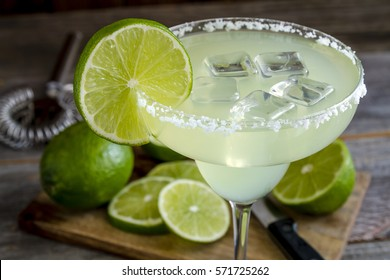 Classic lime margarita cocktail with sliced and whole limes sitting on wooden cutting board