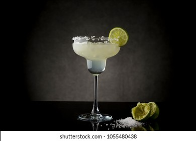 Classic lime margarita cocktail with tequila, triple sec, lime juice, crushed ice and some salt on the rim of a glass, decorated with a slice of lime