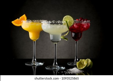 Classic lime margarita, orange margarita and cherry margarita cocktail mix in salt rimmed glasses garnished with slices of lime, orange and cherries