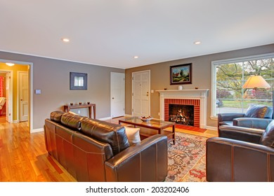 Classic living room interior with fireplace, hardwood floor with rug and leather furniture set