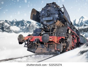 Classic locomotive train on snowy railway amidst the mountains