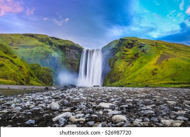 Classic long exposure view of famous Skogafoss waterfall in beautiful twilight during blue hour at dusk in summer, Skogar, south of Iceland