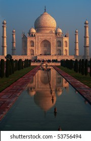 Classic long water fountain reflection image of front facade of far telephoto distance Taj Mahal glowing a colorful red with sunrise light in the morning in Agra, India. Vertical
