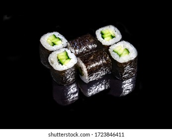 classic Maki roll with cucumber on a black mirror background