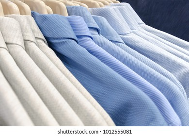 Classic men's shirts made of cotton light cool tones on the clothes hanger in the store. Selling wear in blue color. Photo with shallow depth of field.
