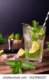Classic Mint Mojito Cocktail in a high ball glass, with ice cube, lime wedge, mint leaves and black and white striped straw, on a wooden background. Copy space