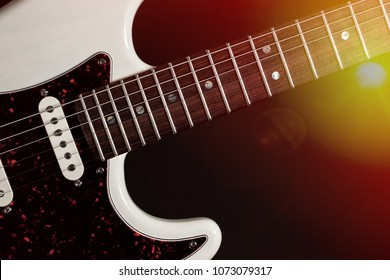 Classic modern electric guitar close-up of fingerboard frets and body with pick-up. Live country  rock music performance white guitar under bright stage lights