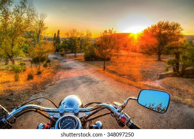 classic motorcycle on the edge of the road at sunset