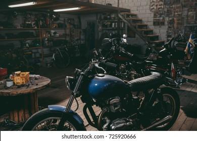 classic motorcycles standing in dark repair shop