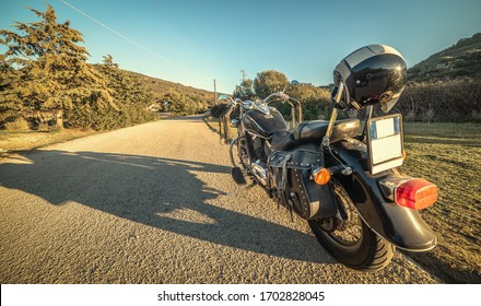 Classic motorycle parked on the edge of a country road at sunset