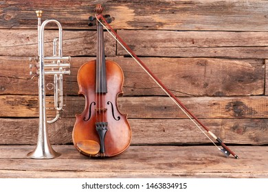 Classic music equipment on wooden background. Violin, trumpet and fiddle stick. Instruments of classical period of music.