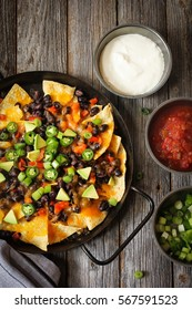 Classic Nachos with Tortilla chips melted cheese sauce jalapeno peppers avocado salsa and sour cream on rustic wooden background / Game day food top down view