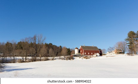 A classic New England red barn in winter with a snow covered field.