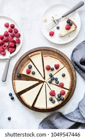 Classic New York cheesecake with fresh raspberries and blueberries on white concrete background, top view