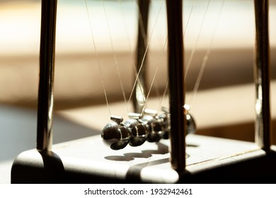 Classic Newtons cradle in sunlight, shallow dof, metal balls still macro, extreme closeup. Momentum, movement physics and common physical laws, simple law of motion abstract concept, nobody