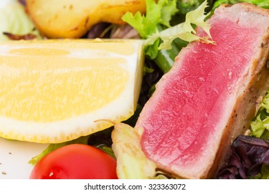 Classic nicoise salad with roasted potatoes and grilled tuna. Macro. Photo can be used as a whole background.