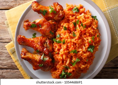 Classic Nigerian Jollof Rice with fried chicken wings close-up on a plate. horizontal top view from above