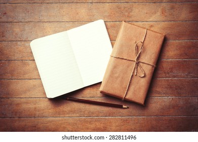 Classic notebook and pencil with parcel on wooden background. Photo in old color image style