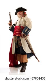 Classic old bearded pirate captain in authentic looking costume standing defiantly with his legs apart and gun upraised. Vertical format with copy space.