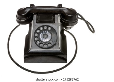Classic old black rotary dial-up telephone instrument, closeup frontal view with the handset in place over a white studio background