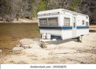 Classic Old Camper Trailer Near A Calm River.