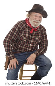 Classic Old West style cheerful cowboy has felt hat, grey whiskers, revolver. Seated on stool. Isolated on white, vertical, copy space.