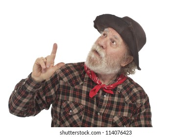 Classic Old West style cowboy with battered felt hat and whiskers looks up and points. Isolated on white, horizontal, copy space.
