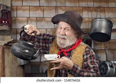 Classic Old West style cowboy cook with felt hat, grey whiskers, red bandana. He is ready to pour tea into a white china tea cup.