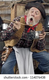 Classic Old West style cowboy with felt hat, grey whiskers, red bandana. He sits on a stool eating beans from a saucepan. Camp cookware and wood shingles in background.