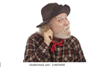 Classic Old West style cowboy with felt hat and grey whiskers pulls on his ear and considers an idea.