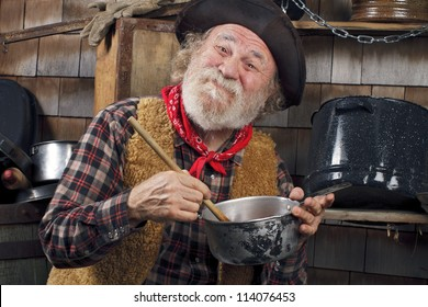 Classic Old West style cowboy with felt hat, grey whiskers, red bandana. He stirs a saucepan with a wooden spoon. Camp cookware and wood shingles in background.
