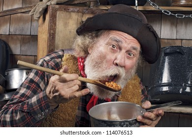 Classic Old West style cowboy with felt hat, grey whiskers, red bandanna. He sits and eats beans from a saucepan. Camp cookware and wood shingles in background.