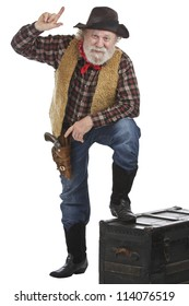 Classic old west style cowboy points up. He has felt hat, grey whiskers, revolver, and stands with one foot up on a wooden chest. Isolated on white, vertical, copy space.