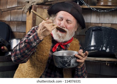 Classic Old West style cowboy with felt hat, grey whiskers, red bandanna. He closes eyes and savors food in a saucepan. Camp cookware and wood shingles in background.