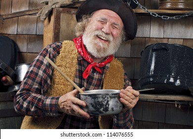 Classic Old West style cowboy with felt hat, grey whiskers, red bandana. He holds a saucepan. Camp cookware and wood shingles in background.